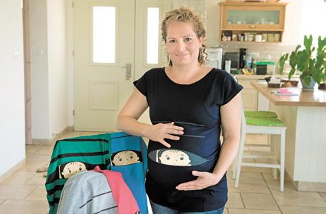 עינת כרמל עם בגדי ההיריון שעיצבה. סאגה ארוכה של קשיים ביורוקרטיים