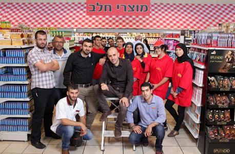 """בלאל (יושב במרכז) ומוחמד (לידו בחולצה שחורה) סלאח עם עובדי הסניף של קינג סטור בנצרת עלית. """"כל מה שקרה לפני 15 שנים אצל היהודים מתחיל לקרות אצלנו"""""""