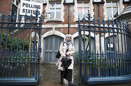 משאל העם בריטניה האיחוד האירופי אישה מוסלמית יוצאת מהקלפי בצפון לונדון, צילום: רויטרס