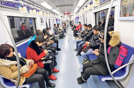 נוסעים ברכבת בבייג'ינג גולשים בסמארטפונים. פייסבוק וטוויטר חסומות בסין, והתחליפים המקומיים נתונים לפיקוח מתמיד