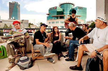 """מרשק (עם הגיטרה) עם סתיו שפיר ופעילים נוספים, על גג """"בית העם"""" ברוטשילד. שימש """"ערוץ הטלוויזיה של המחאה"""""""