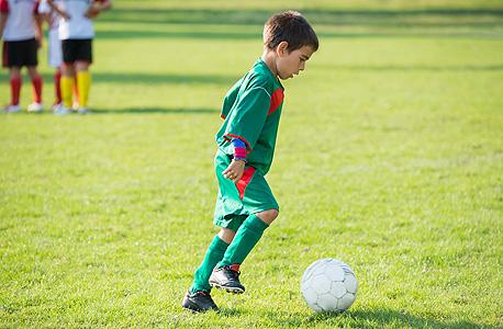 ילד משחק כדורגל. יש לכך מנבאים פיזיולוגיים, חברתיים ופסיכולוגיים
