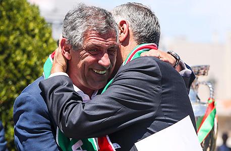 """פרננדו סנטוס המאמן מתחבק עם רבלו דה סוזה, יו""""ר ההתאחדות לכדורגל. התחיל כמנהל שירותים טכניים במלון"""