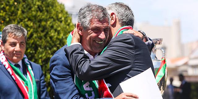 """פרננדו סנטוס המאמן מתחבק עם רבלו דה סוזה, יו""""ר ההתאחדות לכדורגל. התחיל כמנהל שירותים טכניים במלון, צילום: איי אף פי"""
