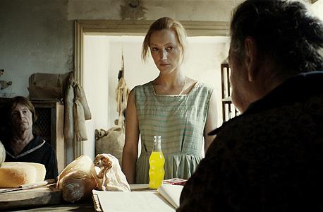 """סט הסרט """"לוויה בצהריים"""" (2014): צרכניה במושב; מעצבת: כרמלה סנדרסון. """"הגר, הדמות הראשית, לא הקימה את הבית שבו היא חיה. היא הגיעה מתל אביב, ושום דבר ממנה לא עבר איתה. תמיד דאגתי שהמקום ייראה קצת דפוק: מנורה שרופה, כיסוי מיטה פרום, שידה בלי מגירות. רציתי לייצר תחושה שבורה, לא מלאה, לא שלמה"""""""