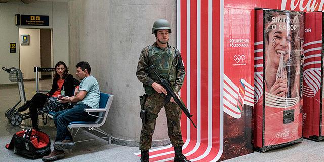 """חייל ברזילאי """"שומר"""" על קוקה־קולה. האולימפיאדה הנוכחית תקבע את עתיד החסויות האישיות, צילום: איי אף פי"""