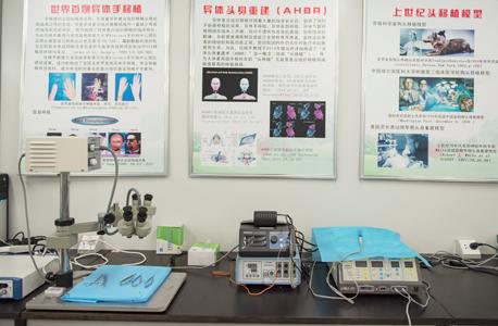 """הפוסטרים במעבדה של שיאופינג רן בבית הספר לרפואה בחרבין. צעיר חולה סרטן נסע ברכבת יותר מ־1,600 ק""""מ רק כדי להתחנן להיות המנותח הראשון"""