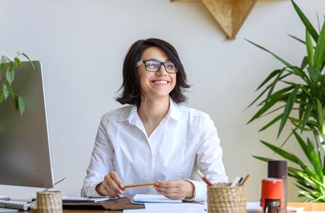 אישה במשרד עם עציצים (אילוסטרציה)