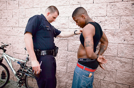שוטר בודק צעיר ששתה אלכוהול ברחוב, בלוס אנג'לס. האלגוריתמים נועדו להילחם בגזענות. מה נשאר מזה?