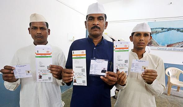 אסירים בכלא בעיר בהופאל בהודו מציגים את תעודות האדהאאר שלהם. הפרויקט מעלה שאלות של תרבות, זהות ופוליטיקה