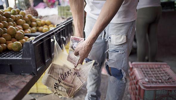אוספים כסף בשוק בשקיות, צילום: בלומברג