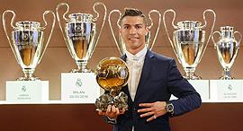 כריסטיאנו רונלדו עם גביע השחקן המצטיין של השנה בלון ד'אור וגביעי ריאל מדריד, צילום: איי אף פי