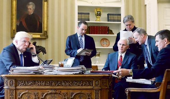 """בנון (עומד עם דפים בידיו) עם טראמפ ועמיתיו בחדר הסגלגל, בשבת. """"אם נצליח לספק את הסחורה אנחנו נמשול למשך 50 שנה"""""""