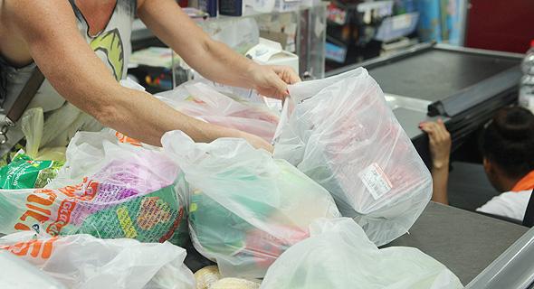 לקוחות אורזים מצרכים ב שקיות ניילון ב קופה ב סניף ויקטורי ב תל אביב, צילום: עמית שעל