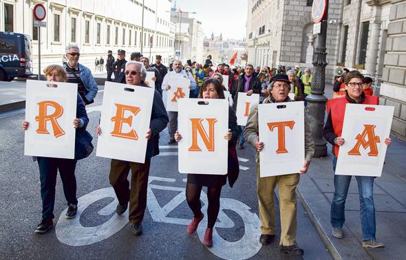 """הפגנה במדריד, ספרד, למען הכנסה־לכל. """"שוק העבודה אינו בר־תיקון. הפסדנו במירוץ נגד מכונות שהחליפו עובדים"""""""