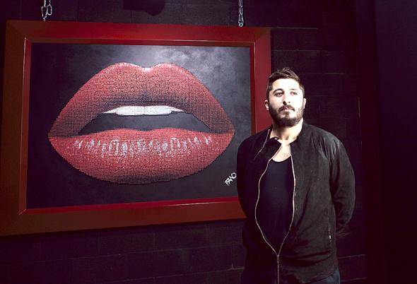 """ג'ואן לורי בוטבול, בעלי הגלריה באלנבי, על רקע העבודה  """"AK Lips-47"""" של פאנו, שעשויה מ־8,000 ברגים. """"וואו, זה המוטו של המקום. כמו שאומרים על פרארי"""""""