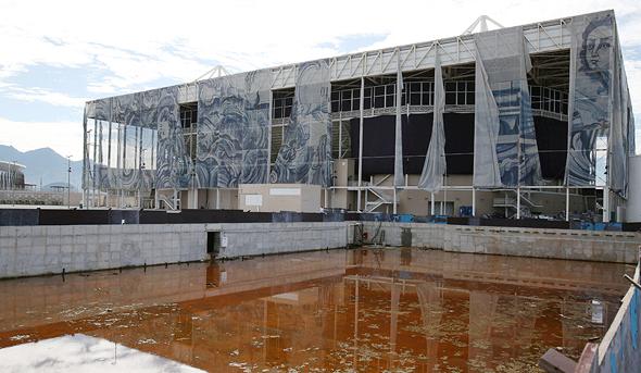 """בריכת השחייה האולימפית בריו. במשחקי ריו 2016 נרשמו פליטות גזי חממה בסך של 3.6 מיליון טון של פחמן דו-חמצני, מספר שלכאורה הופחת על ידי התחייבות של ממשלת ברזיל """"לפצות"""" על הפליטות באמצעות מימון פרויקטים של שתילת עצים ביער האמזוני – תכסיס חשבונאי מוכר שממשלות וגופים אחרים נוקטים בו כדי לצמצמם, לכאורה, את ההשפעה הסביבתית שלהם , צילום: רויטרס"""
