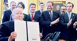 דונלד טראמפ מציג את הצו הנשיאותי האחרון מלווה במנהיגי עולם העסקים, צילום: בלומברג