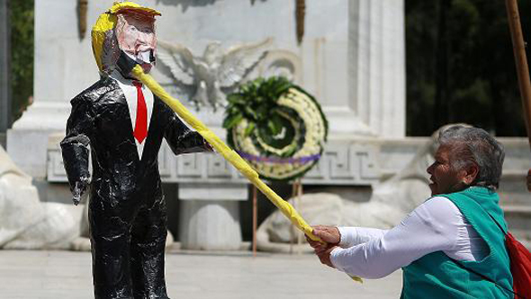 אזרח מקסיקו מכה בובה בדמותו של טראמפ, צילום: גטי אימג