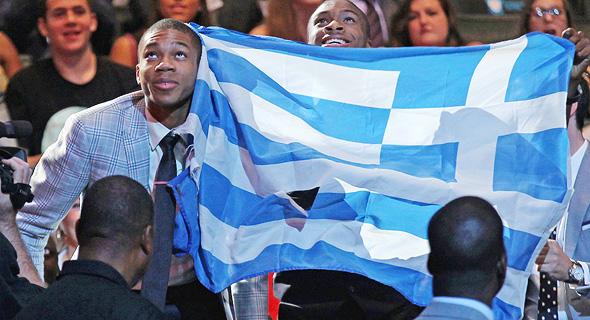 """אנטטוקומפו עם דגל יוון בעת ההכרזה על בחירתו בדראפט 2013. """"אם אתה נותן לשימפנזה בננה ודגל, האם הוא נהפך ליווני?"""" , צילום: גטי אימג"""