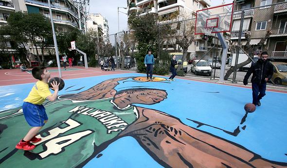 """מגרש כדורסל מכוסה בציור של אנטטוקומפו בשכונת ילדותו ספוליה באתונה. """"ליוון יש חלק אדיר במה שאני"""", צילום: אי פי איי"""