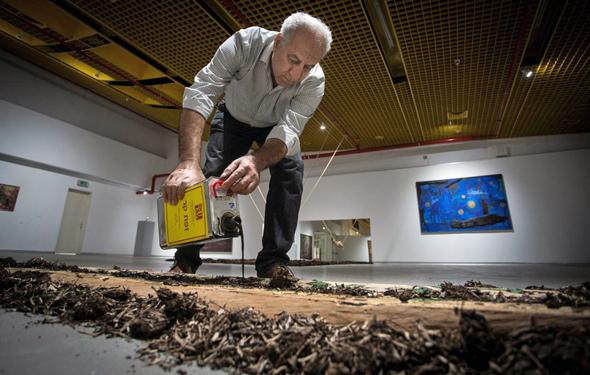 """סעיד במהלך הקמת התערוכה. """"המשך ישיר לדרך בה הייתי מצייר על האדמה בתור ילד"""", צילום: גיל נחושתן"""