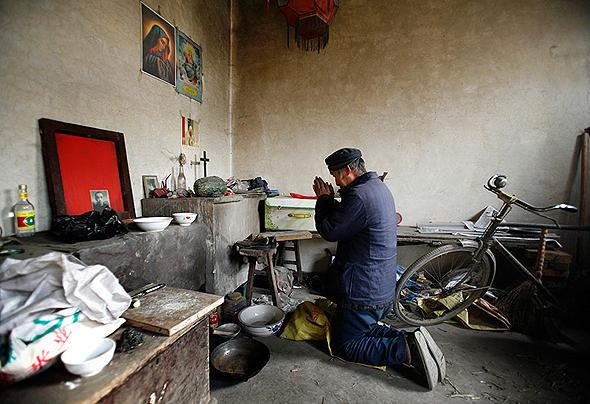נוצרי סיני מתפלל בביתו