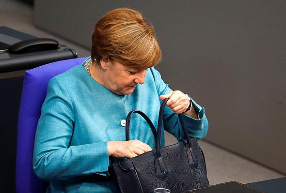 אנגלה מרקל קנצלרית גרמניה מסתכלת בתיק, צילום: רויטרס