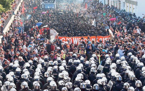 """מפגינים נגד ועידת G20 בהמבורג, בתחילת החודש. """"אנחנו קצת כמו הדמות המצוירת שפוסעת אל מעבר לשפת הצוק"""