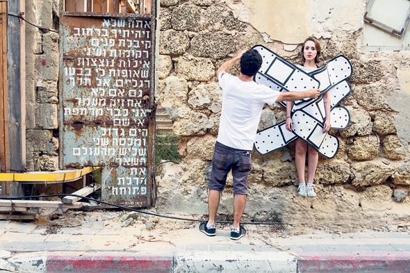 """מינץ ודדה על רקע (ובתוך) עבודות שלהם, נווה צדק, תל אביב. """"בניגוד למוזיאון, אמנות רחוב מפתיעה אותך ונקשרת לחוויה שאתה עובר"""""""