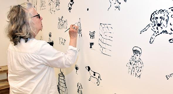 """מאירה קלמן מציירת לתערוכה """"כלבים וחתולים"""" על קיר מוזיאון ישראל"""