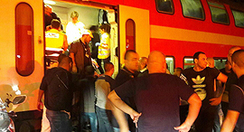 נוסעים ליד הרכבת שפגעה הערב ברכב בלוד, צילום: דוברות איחוד ההצלה