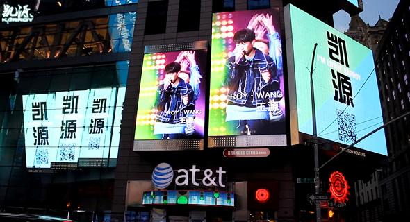 ואנג ג'וקאי על מסכי פרסום בטיימס סקוור בניו יורק, מתנה ממעריציו ליום הולדתו ה־17
