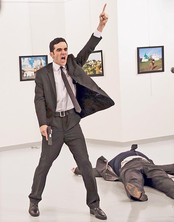 המתנקש (משמאל) והשגריר אנדריי קרלוב מוטל על הרצפה, בצילום הזוכה בתערוכת הצילום World Press Photo.