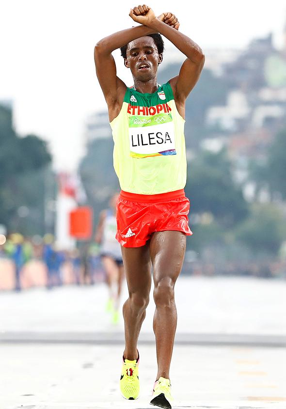 הרץ האתיופי, זוכה מדליית הכסף במרתון באולימפיאדת ריו, פייסה לילסה, מצליב את ידיו לאות הזדהות עם בני האורומו