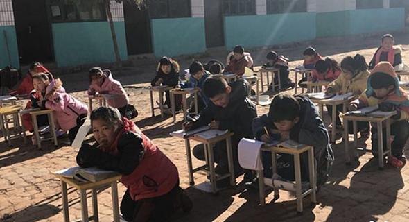 תלמידים בסין לומדים בחצר כדי להתחמם בשמש