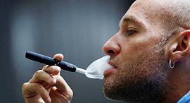 עישון סיגריה אלקטרונית IQOS , צילום: רויטרס