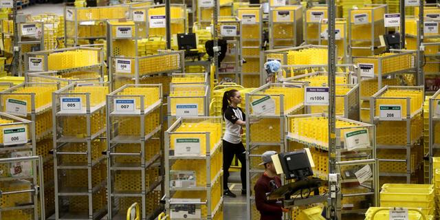 פועלים במחסן אמזון, צילום: בלומברג