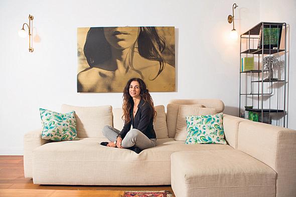 חגית בסלון ביתה. יושבת על ספה שעיצב עבורה כנפו
