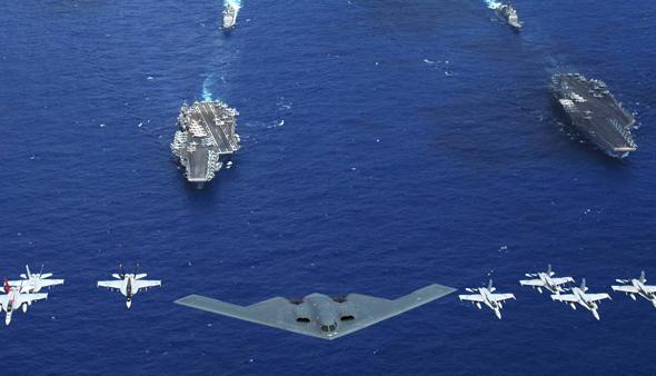 מפציץ B2 מלווה במטוסי F18 של הצי האמריקאי