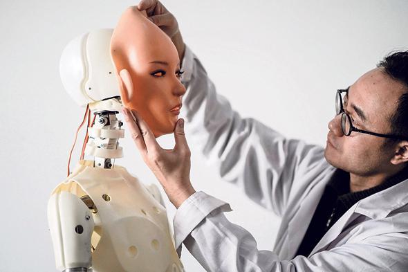 """מדען סיני במעבדת רובוטיקה לייצור """"בנות לוויה"""" רובוטיות לסינים בודדים, בתחילת החודש"""