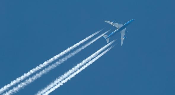 מטוס נוסעים בשיוט, אחריו שובל לבן שנוצר מהתקררות גזי המנוע