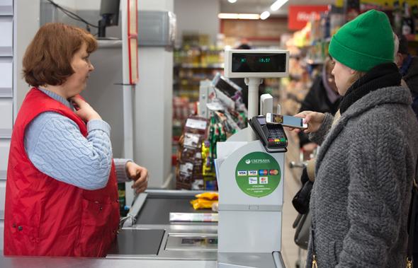 לקוחה בסופרמרקט ברוסיה משלמת באמצעות אפל פיי apple pay, צילום: בלומברג