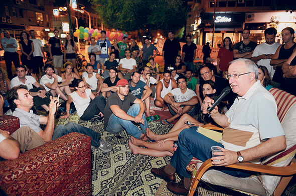 פרופ' מנואל טרכטנברג בשיחה עם מפגינים בכיכר המדינה בתל אביב, צילום: יובל חן