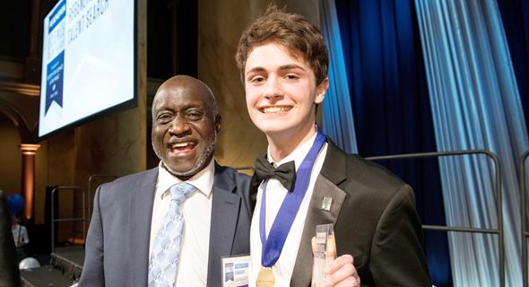 """פירסטר במרץ, בטקס קבלת הפרס בתחרות Regeneron Science Talent Search, עם אחד ממוריו בתיכון. """"המחקר הזה מראה את הכוח של מתמטיקה, זכיתי ליישם אותה על העולם האמיתי"""""""