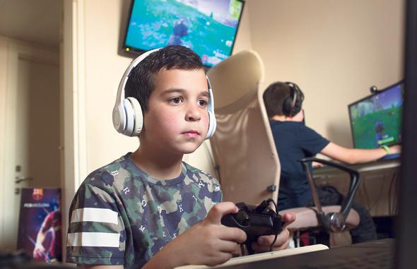 """מימין: תומר (12) ואיתן (8.5) מנדלסון, גני תקווה. """"יש לנו מחשב גיימינג עם שלושה מסכים, ועוד מחשב. חברים באים אלינו עם הפלייסטיישן והאקס בוקס שלהם. ככה אנחנו משחקים יחד מאותו מקום"""""""