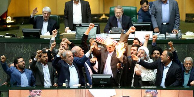 """שריפת דגל ארה""""ב בפרלמנט האיראני, אתמול. רוב האיראנים לא נהנו מפירות ההסכם , צילום: איי אף פי"""