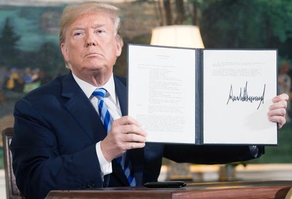 """נשיא ארה""""ב דונלד טראמפ חותם על צו נשיאותי ליציאה מהסכם הגרעין שלשום, צילום: איי אף פי"""