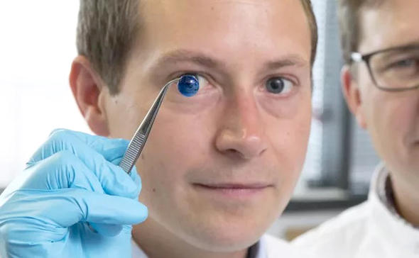 A technician holds up a 3D printed cornea. Photo: Newcastle University
