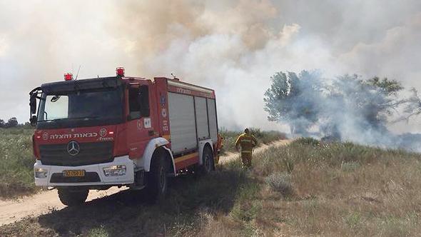 כבאית מכבה את השריפה בכרמיה שפרצה כתוצאה מעפיפון תבערה, צילום: תומר עופרי, רשות הטבע והגנים